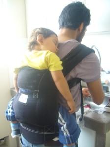 Omar lavando con Caetano dormido y porteado en la espalda.